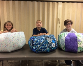 Three young seamstresses working on their gumdrop pillows